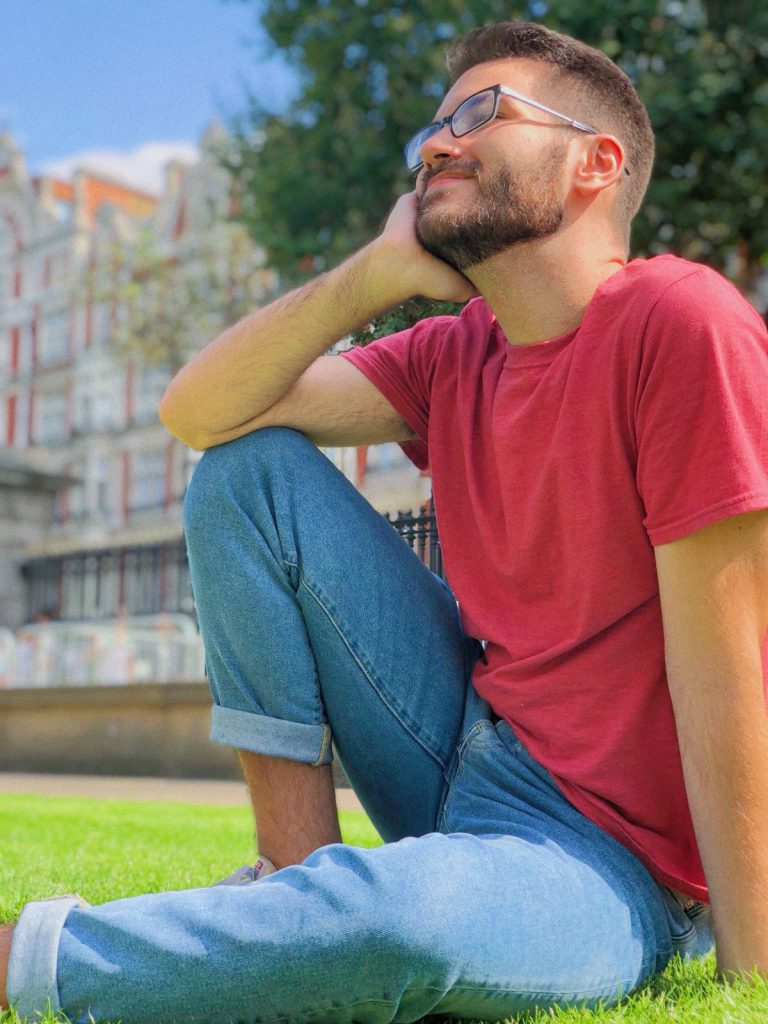 Austin sits in the grass in a square in London